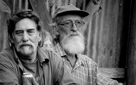 grayscale photography of two men sitting beside each other