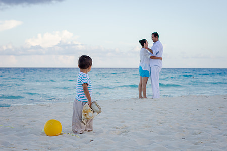 boy wearing white t-shirt staring on man and woman standing on shoreline