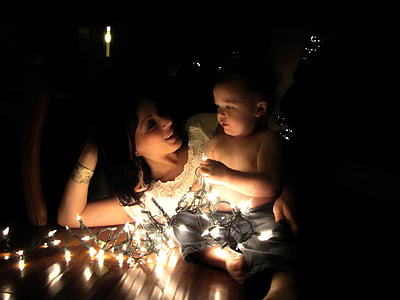photo of woman laying on brown wooden floor with topless baby holding stringed lights