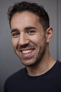 smiling man in black crew neck shirt beside a white wall