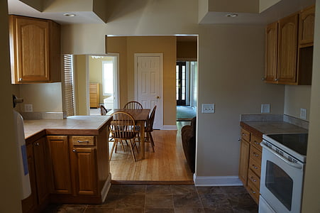white induction range oven beside brown wooden kitchen cupboard