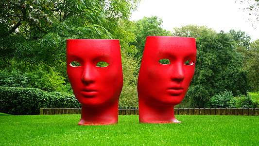 two red mask statue on green grass surrounded by trees