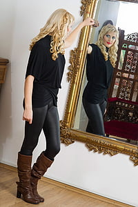 woman looking her reflection on the mirror