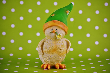 duckling biting yellow petaled flower figurine on green and white polka-dot surface
