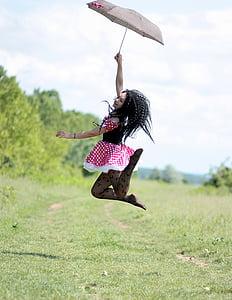 woman holding umbrella jumping on green grass field
