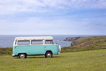 teal and white Volkswagen van parked on green grass field near ocean during daytrime