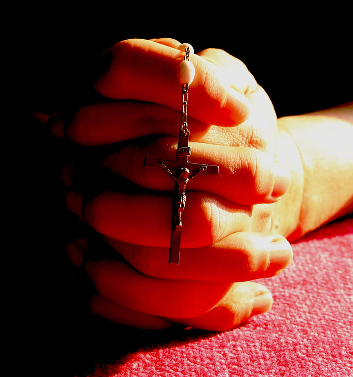 person praying while holding crucifix pendant necklace