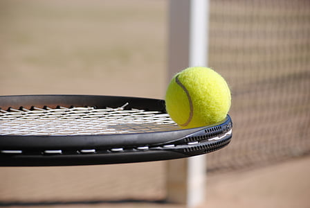 black tennis racket and tennis ball