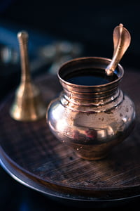 selective focus photography of small jar on brown table beside hand bell
