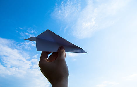 person holding paper plane during daytime