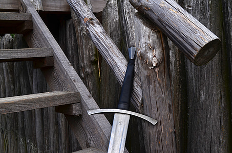 broadsword beside gray wooden staircase