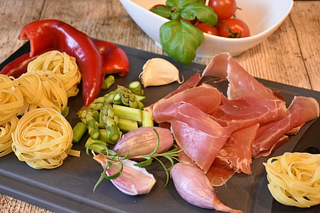 sliced meat, pasta, and vegetables on chopping board