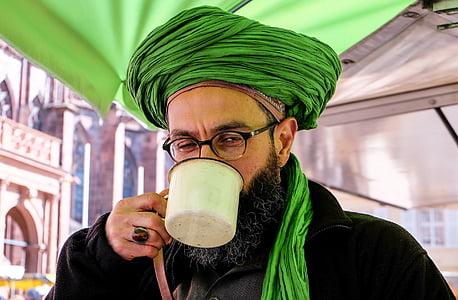 man holding white mug while drinking