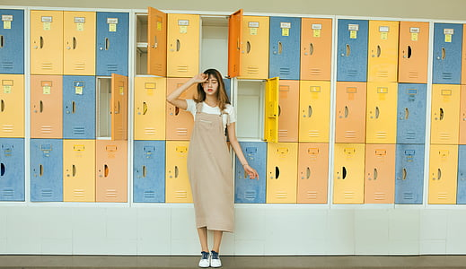 woman wearing brown jumper skirt standing in front of yellow and blue lockers