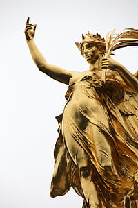 gold statue of a woman with her finger pointing upward