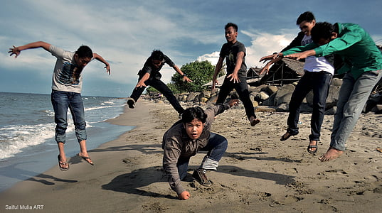 six person doing stunt on sea shore during daytime