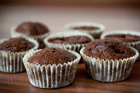 seven chocolate cupcakes on brown wooden surface