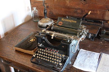 black Remington typewriter beside white printer paper