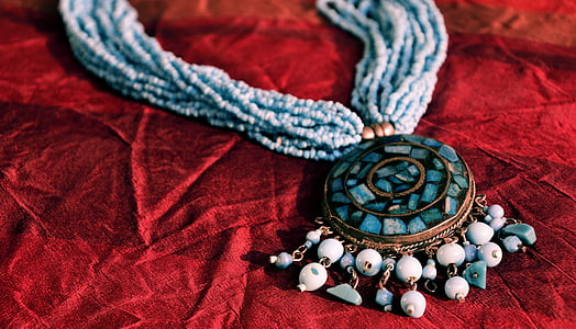 beaded blue stone necklace on red cloth