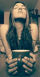 woman holding black ceramic mug