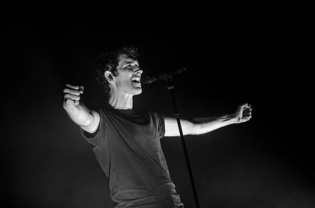 grayscale photo of man singing