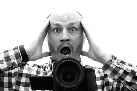 grayscale photo of man screaming with bridge camera in front