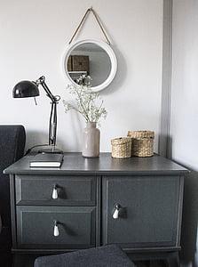 black gooseneck table lamp on gray wooden drawer