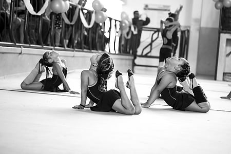 three girls doing exercise grayscale photo