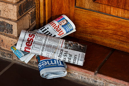 three newspapers on the floor