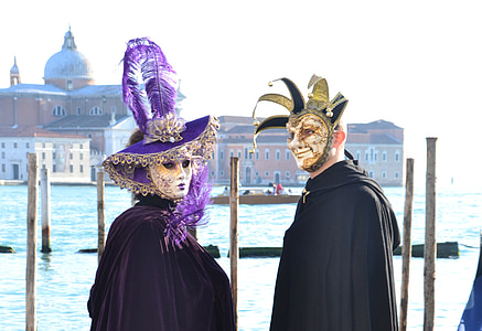 two person wearing masks beside body of water