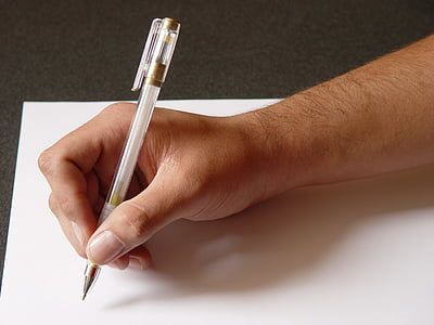 person holding pen writing on white printing paper