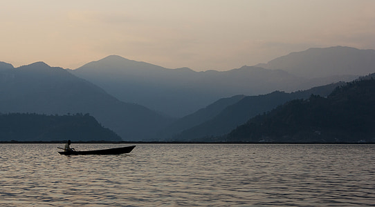person riding boat sailing on body of water during dawn