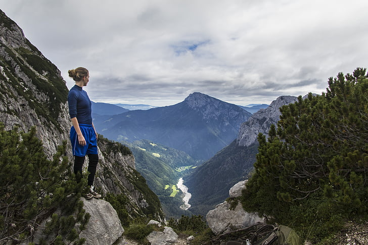 woman standing on rock formation while looking on mountain cliff