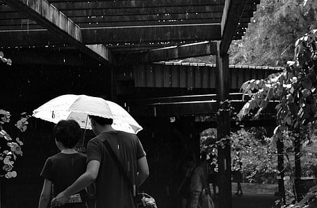 grayscale photo of man and woman under umbrella near brown wooden building