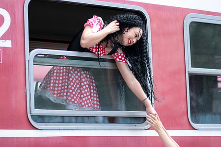 woman reaching hand with person outside train window