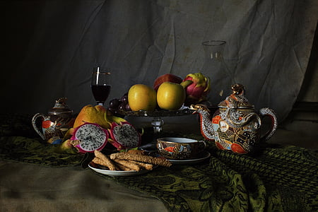variety of fruits and teapot on brown textile
