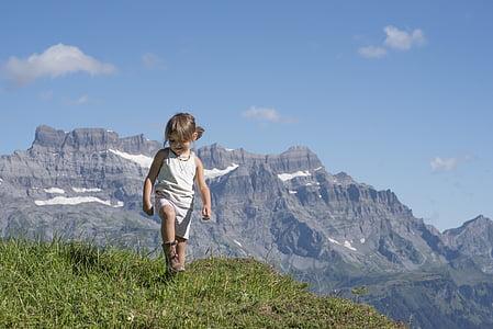 girl standing on grasses within mountain range