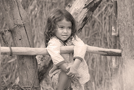 grayscale photo of girl beside log