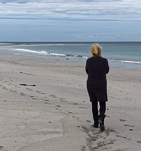 woman walking at seashore under white clouds