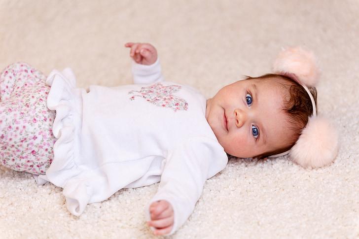 child lying on white fur textile