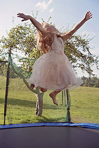 girl in pink dress jumping on trampoline