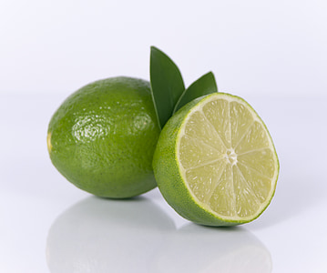 whole and slice of green limes