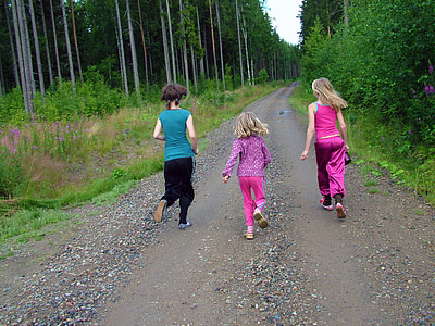 three girls walking on brown pathway