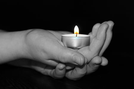 person holding tealight candle holder