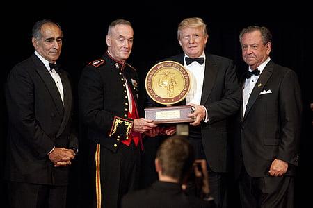 Donald Trump holding award with three men