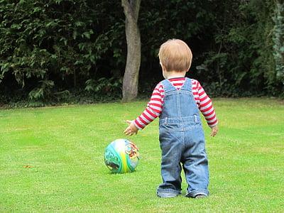 boy walking towards ball at daytime
