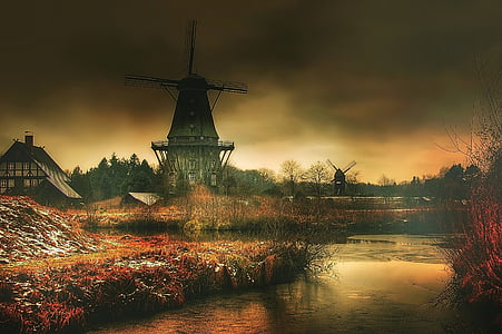 black and gray windmill beside body of water painting