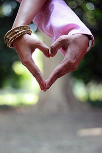 couple's hands forming heart gesture