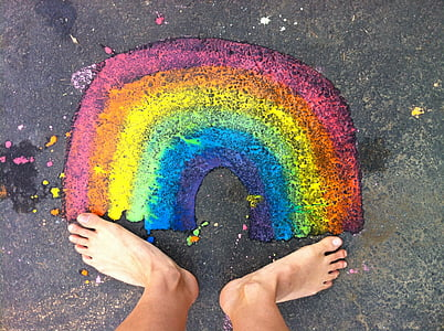 person standing in front of rainbow painting