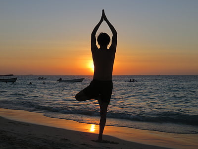 silhouette of person standing on beach doing yoga pose